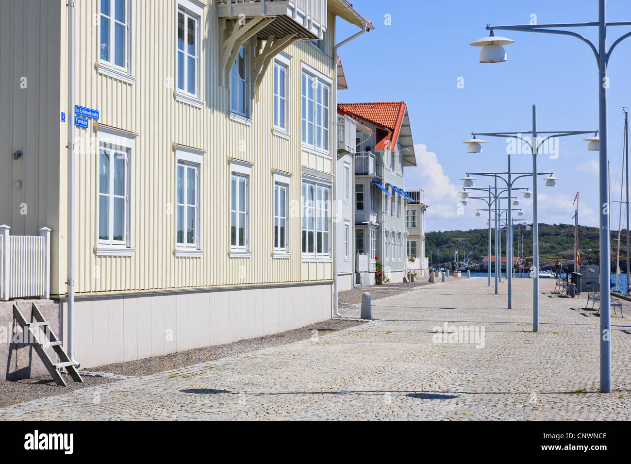 Small apartment house built on the coast with sea view, Boardwalk with street lighting - Stock Image
