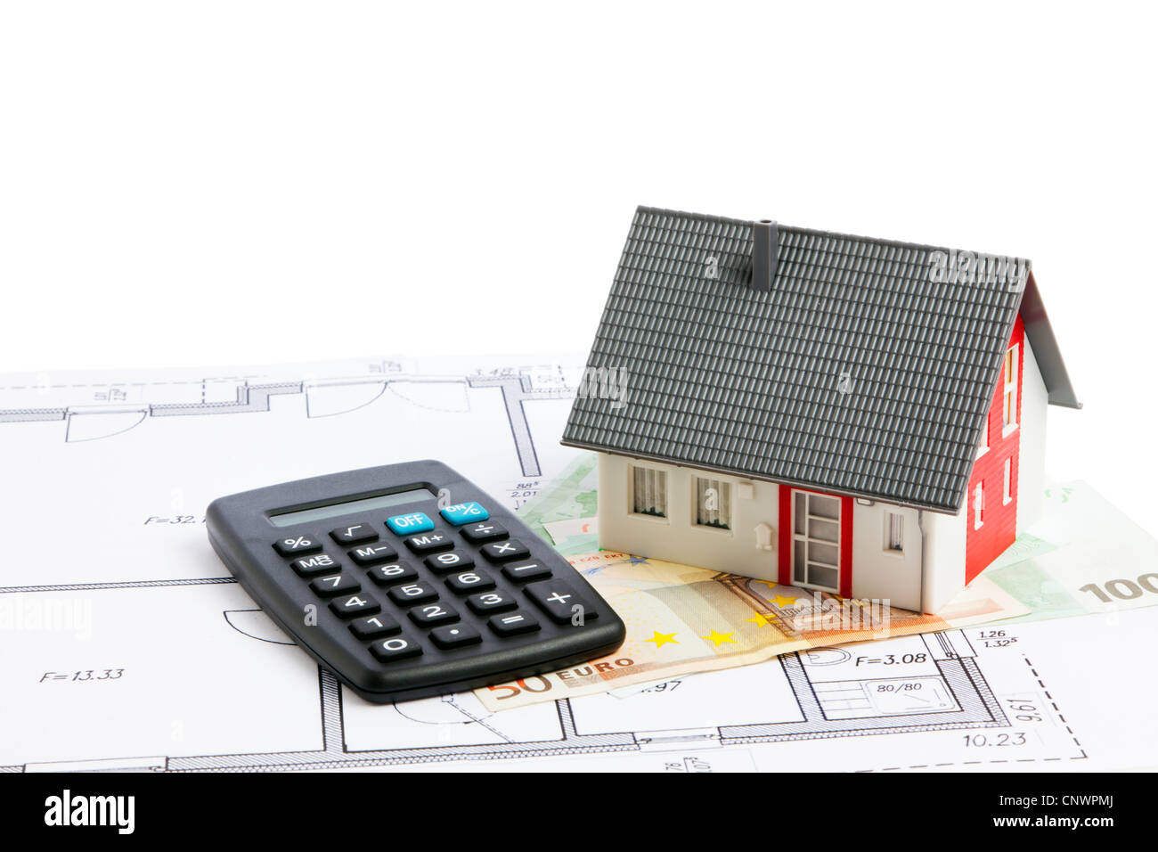 Model of a small house, calculator, money and blueprint - Stock Image