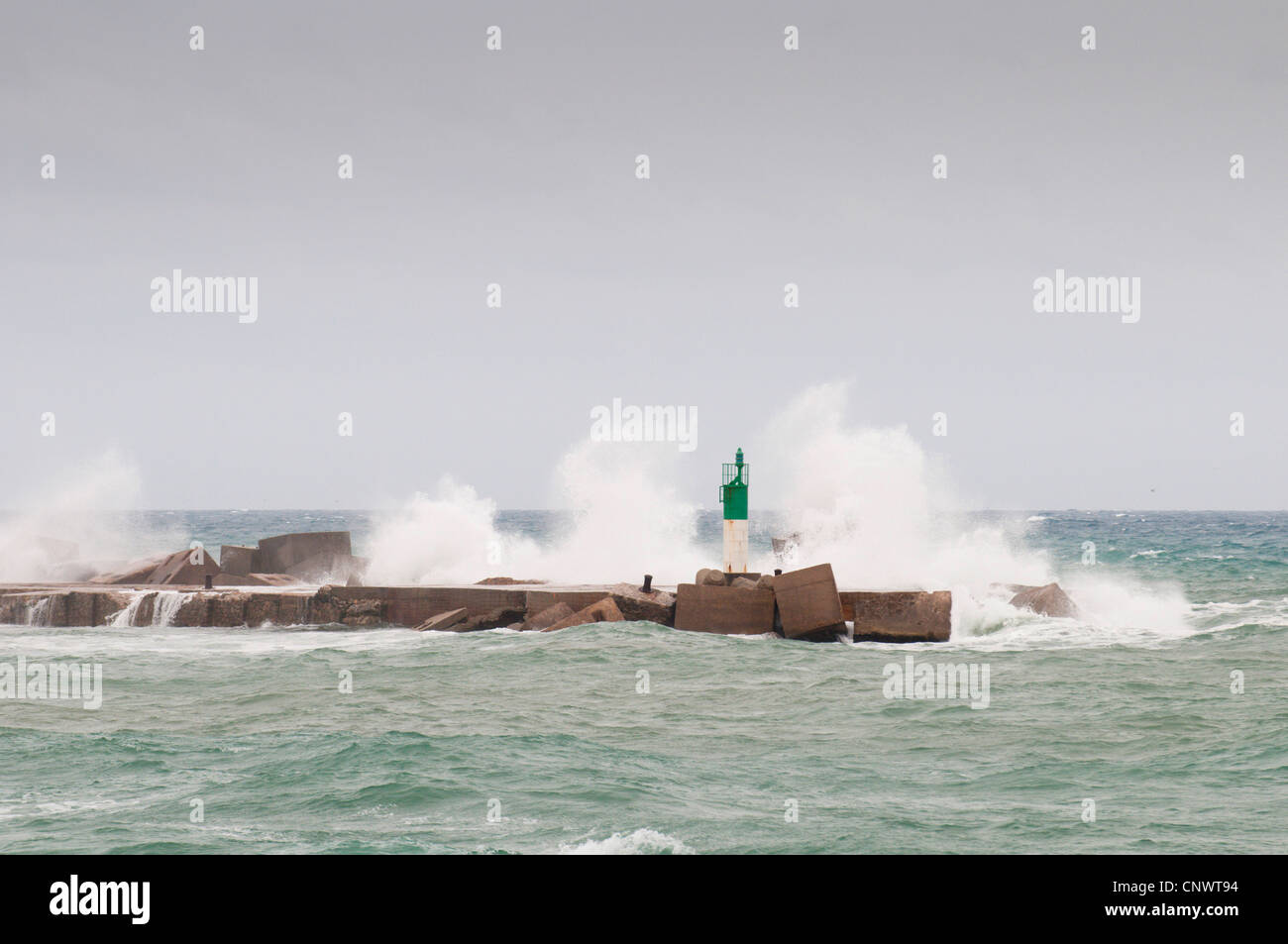breakwaters with beacon in stormy surge, France, Languedoc-Roussillon, Ste - Stock Image