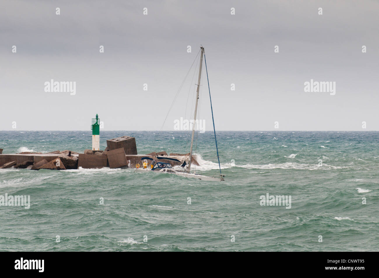 sailboat at stormy surge, in front of breakwaters with beacon, France, Languedoc-Roussillon, S�te - Stock Image