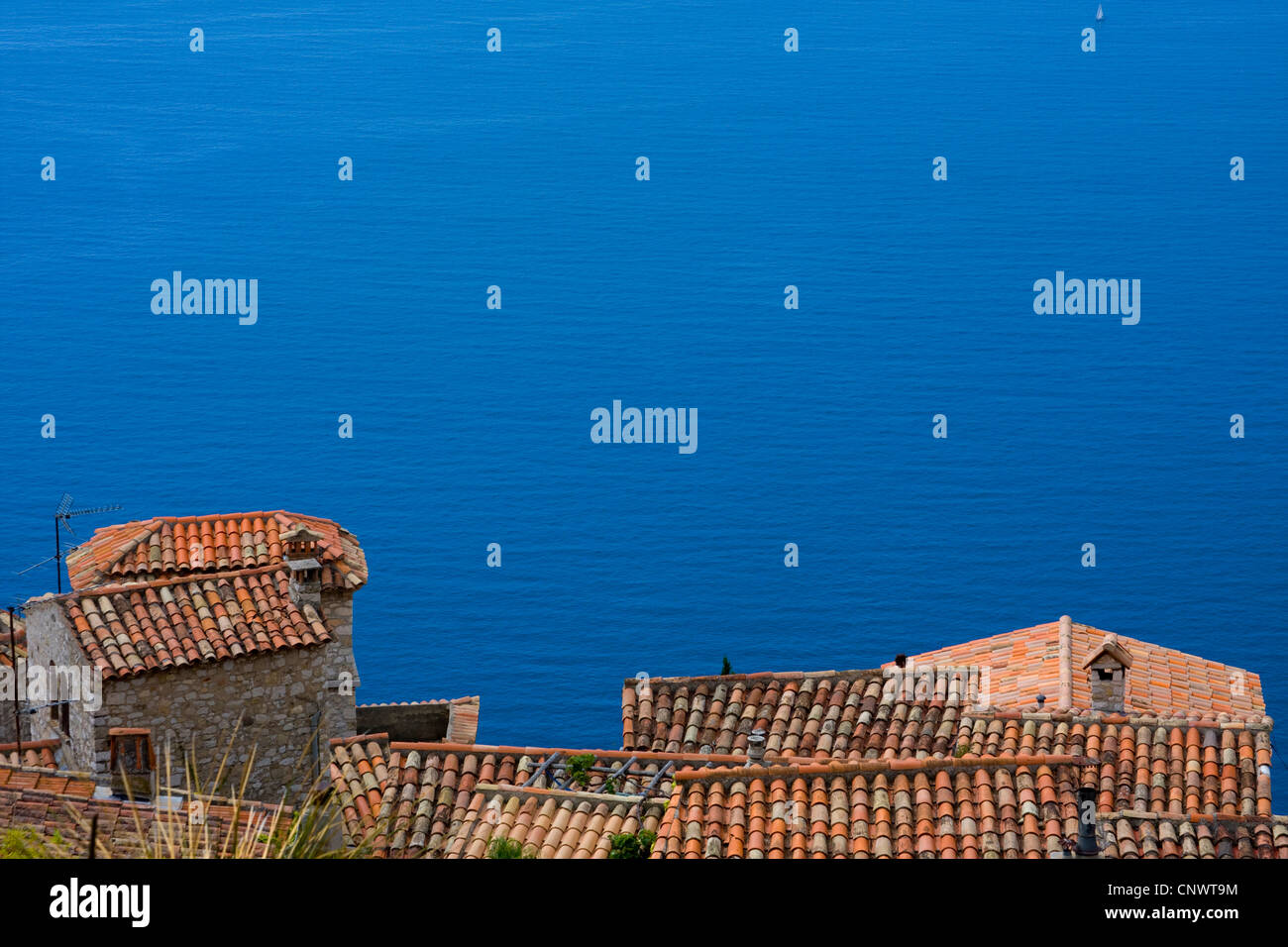 view down the roofs of the village down the steep coast at the open sea, France, �ze - Stock Image