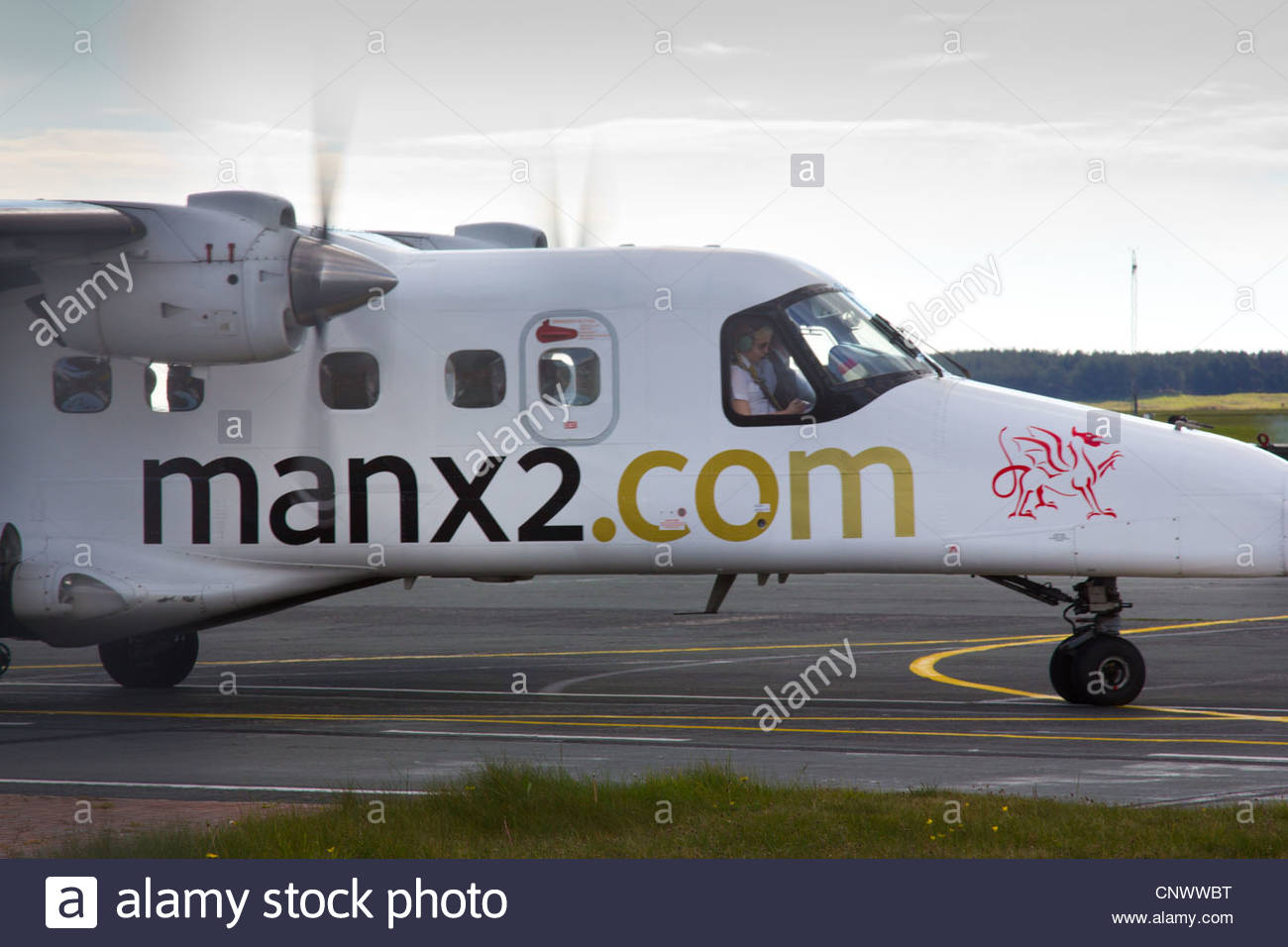Manx2 aircraft arriving at Anglesey Airport terminal, RAF Valley, with pilot visible in cockpit - Stock Image
