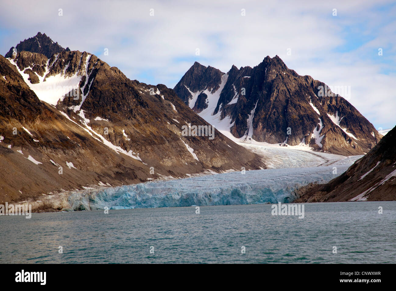 glacier at Magdalena Bay (Magdalenenfjorden) with the melting clear to see at the mountain slopes, Norway, Svalbard, - Stock Image