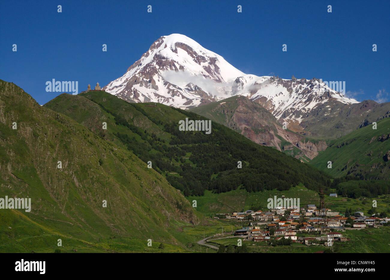dormant stratovolcano Mount Kazbek (5.047 m), the domed Tsiminda Sameba church on the mountain range in the foreground, - Stock Image