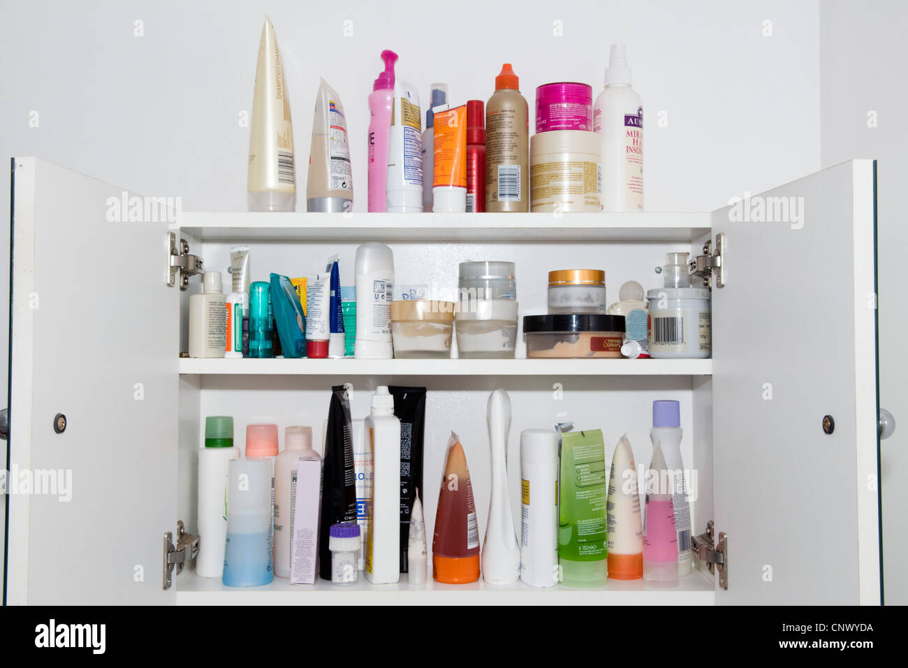 Bathroom cabinet with doors open showing contents of lots of different toiletries - Stock Image