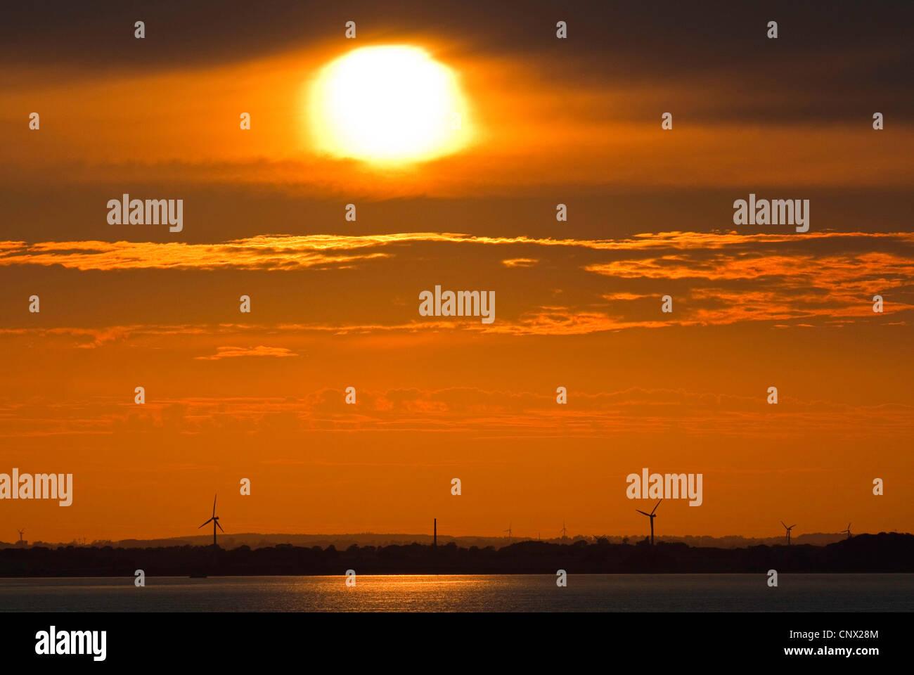 coastline at the Little Belt at sunset with silhouettes of wind wheels, Denmark, Kleiner Belt Stock Photo