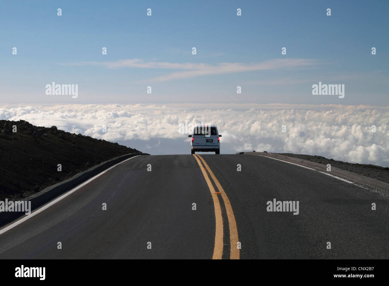 passenger car on a road over the clouds on top of the volcano Haleakala (3000 m), USA, Hawaii, Maui - Stock Image