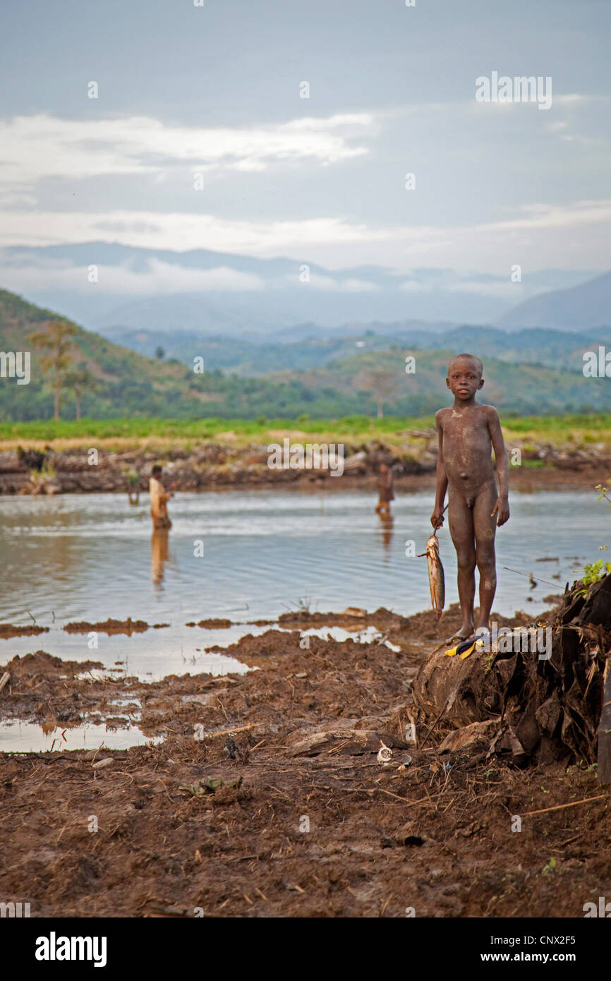 boys fishing in a little lake at the edge of a cleared plantation, Burundi, Rumonge, Rumonge - Stock Image