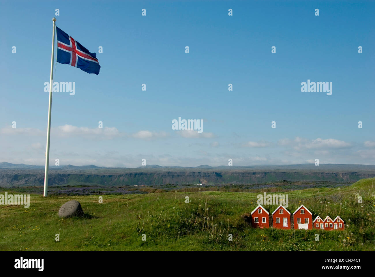 miniature models of sod houses placed in the grass of an elevated plain beside an Icelandic flag, Iceland, Reykjanes - Stock Image