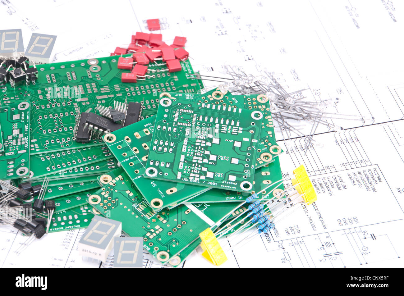 Circuit boards and electronic components with schematics in background - Stock Image