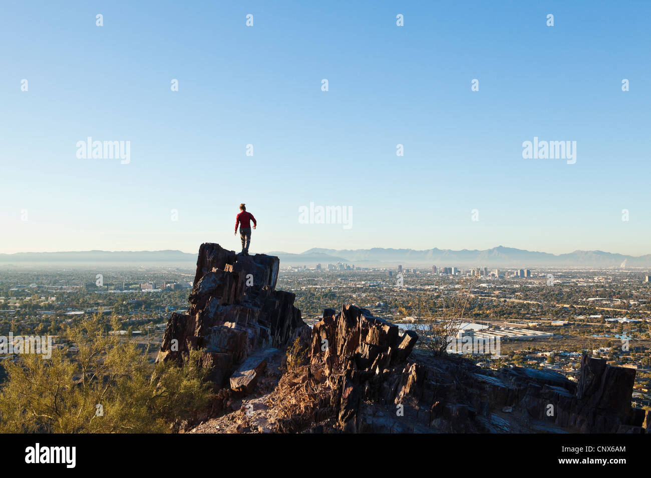 A woman atop a rocky outcrop on Piestewa Peak overlooking Phoenix, Arizona / The Valley of The Sun. - Stock Image