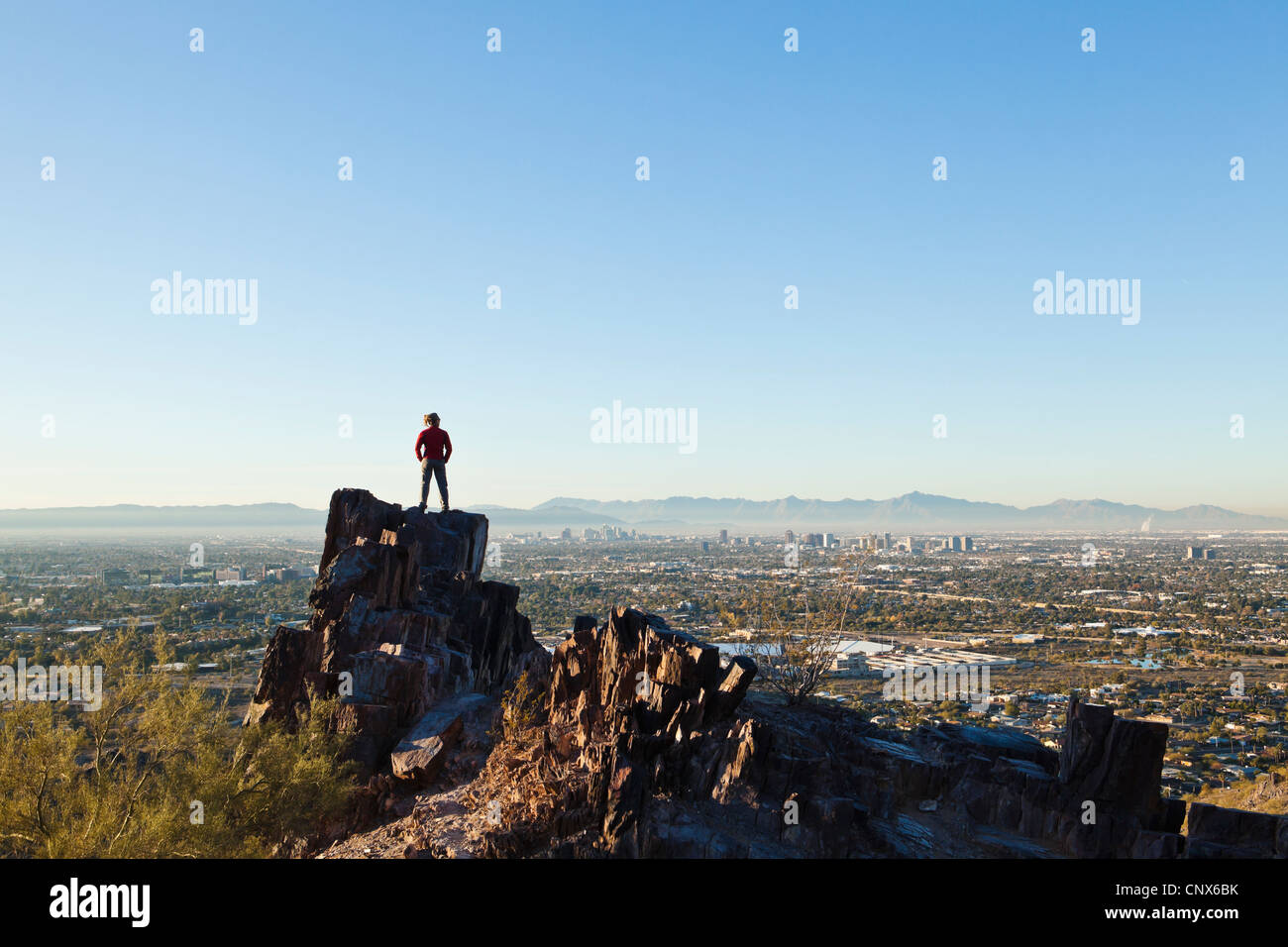 A woman stands atop a rocky outcrop on Piestewa Peak overlooking Phoenix, Arizona / The Valley of The Sun. - Stock Image