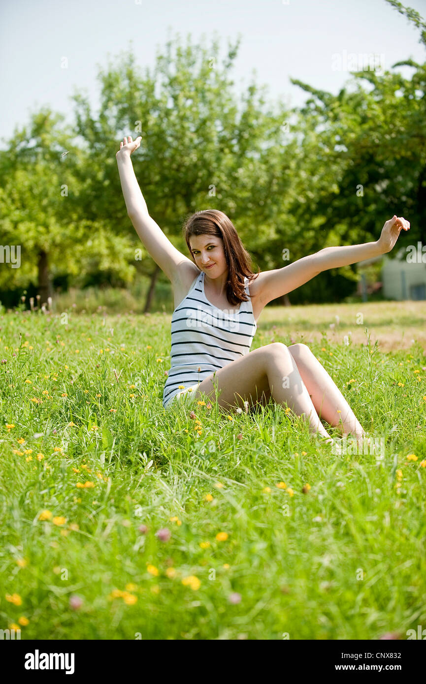 teenage girl sitting in a meadow lolling - Stock Image