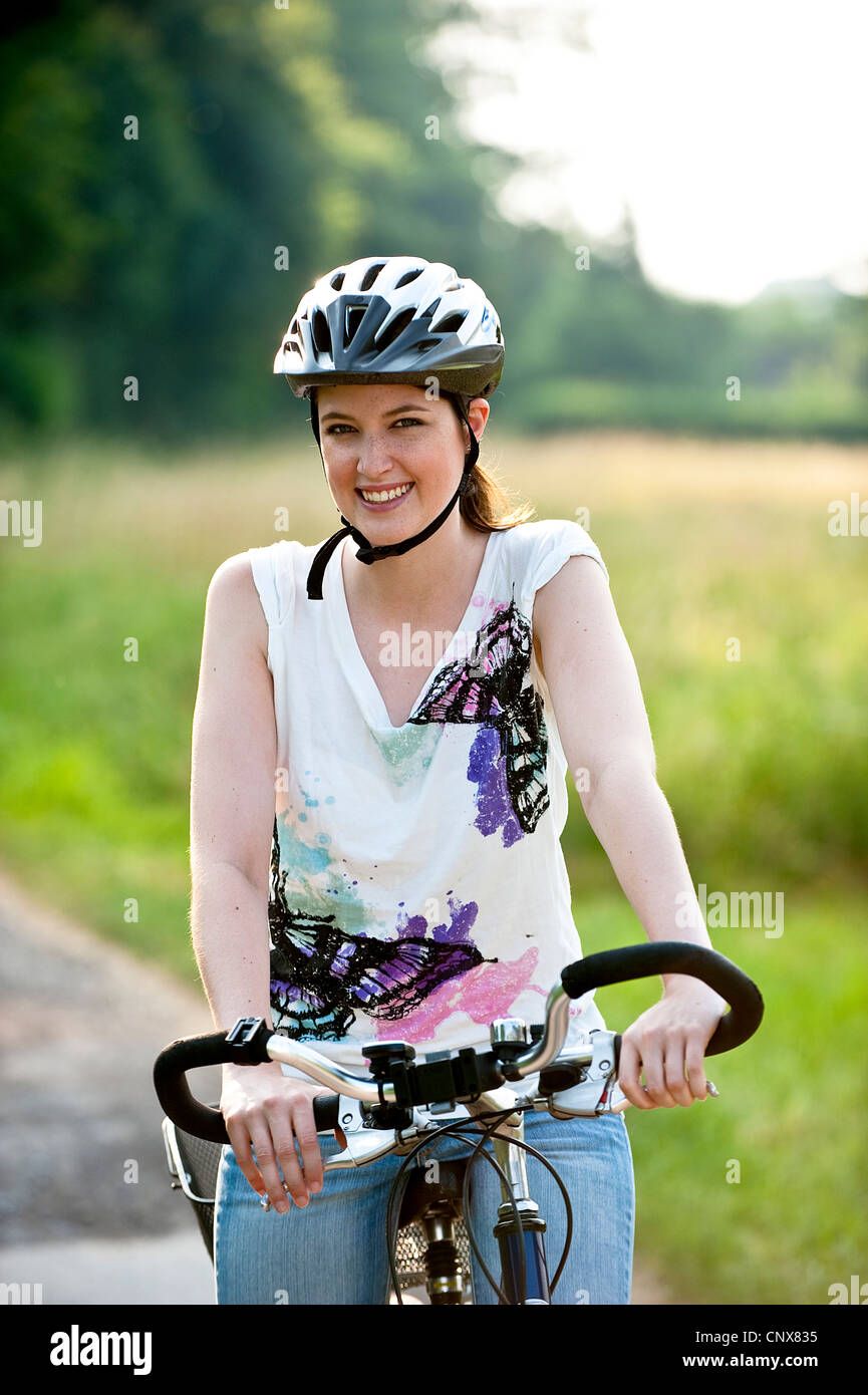 teenage girl standing on a bike on a road at the edge of a forest - Stock Image