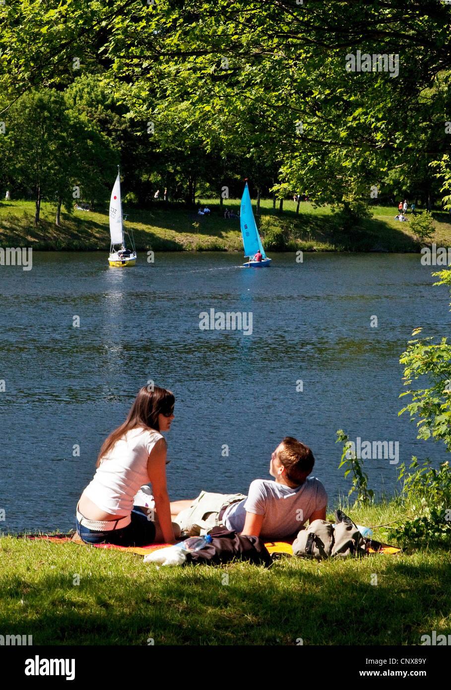 young copule sunbathing at lake Kemande, Kemnader See , Germany, North Rhine-Westphalia, Ruhr Area, Witten - Stock Image