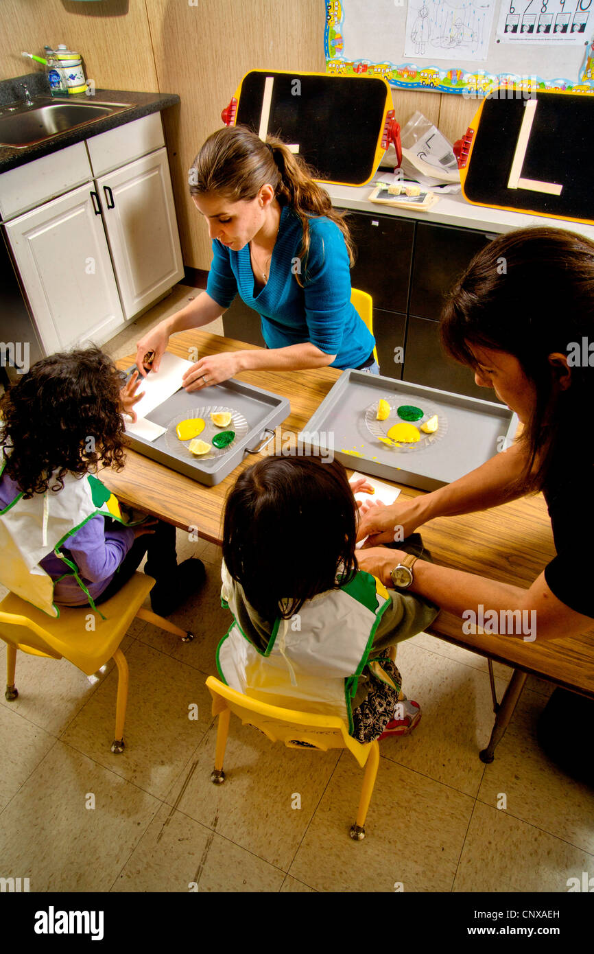 Teachers watch as blind children use yellow and green gel to signify lemon and lime -- both starting with the letter Stock Photo