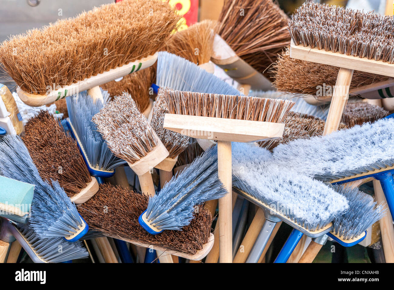 New brooms sweep clean. A lot of different new brooms in a big bunch for sale outside a shop. - Stock Image