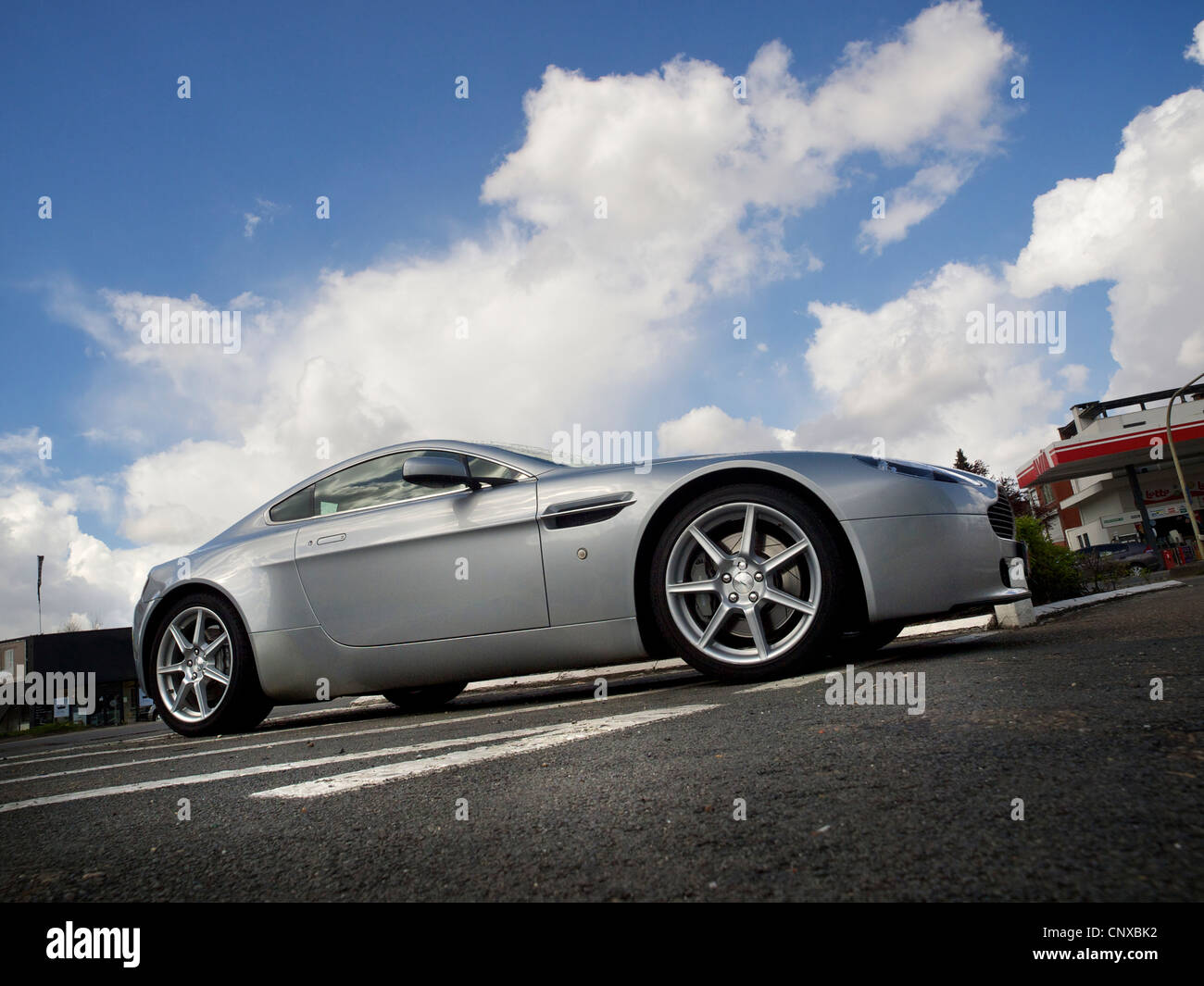 Aston Martin luxury sportscar parked with dramatic sky in the background - Stock Image