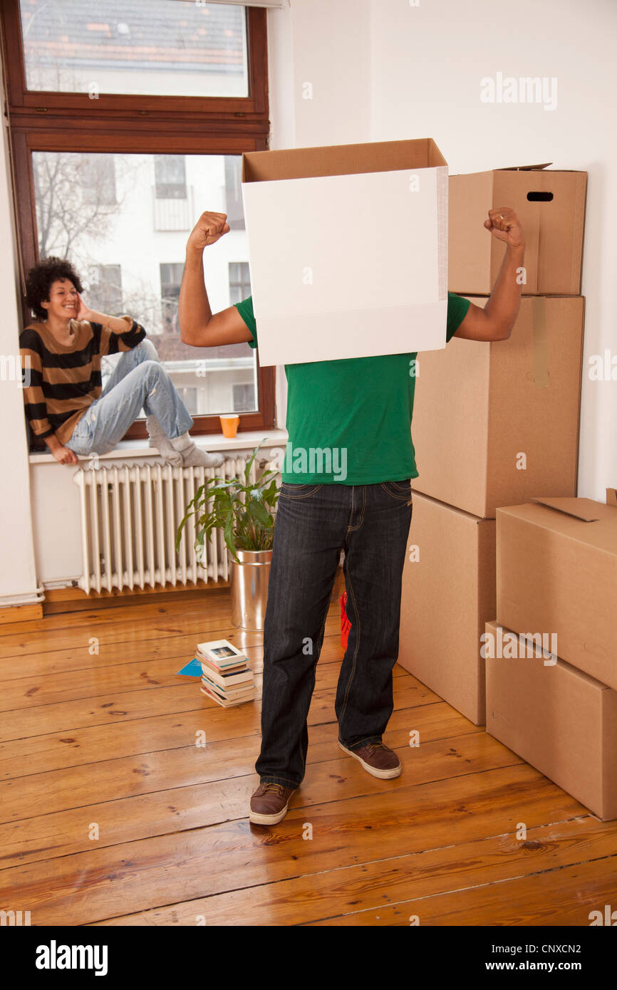 A man with a box on his head flexing his muscles while woman watches - Stock Image