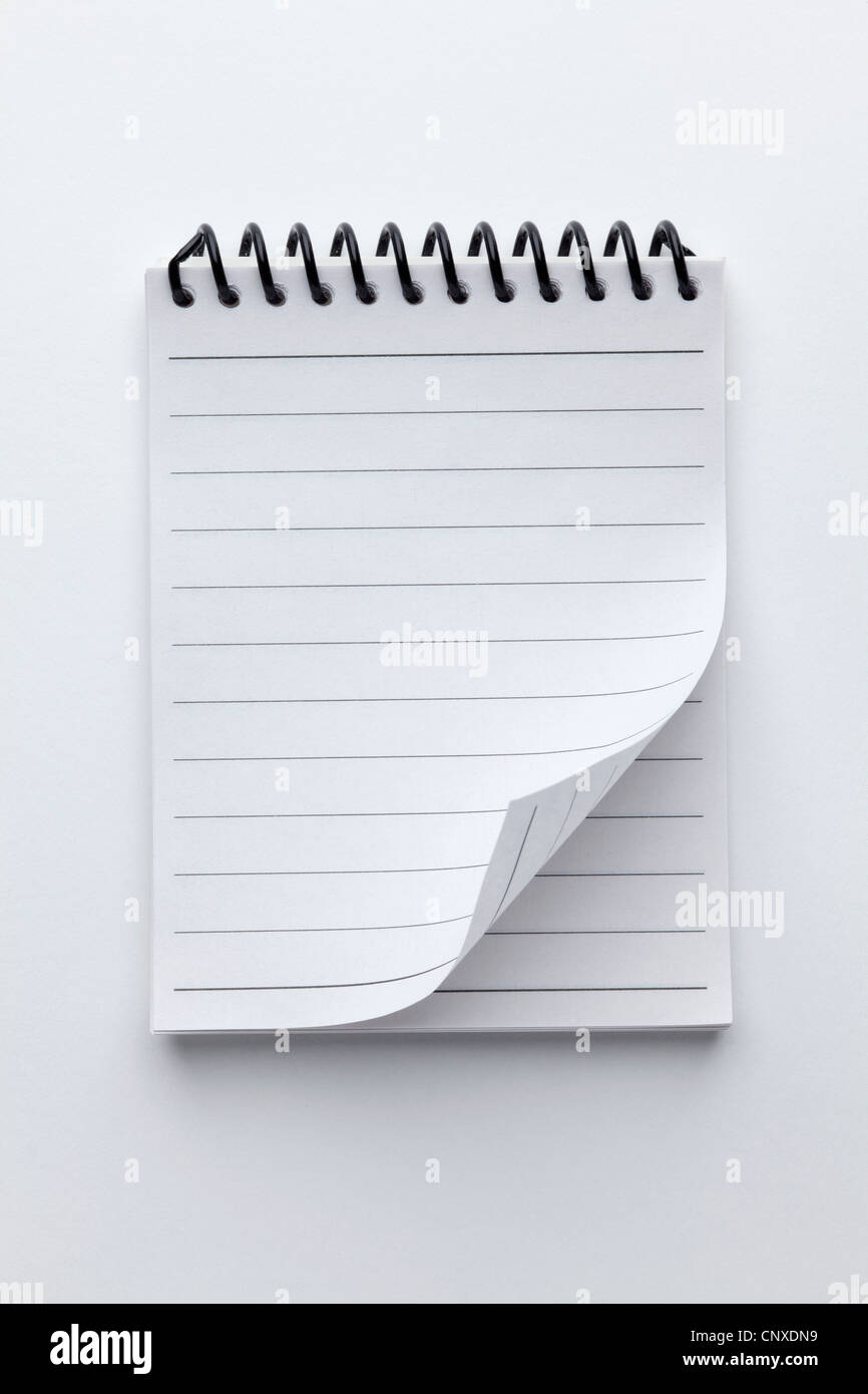 A spiral notepad with lined paper and a curled up page corner - Stock Image