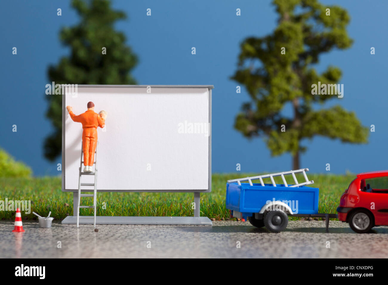 A diorama of a miniature worker billboard posting - Stock Image