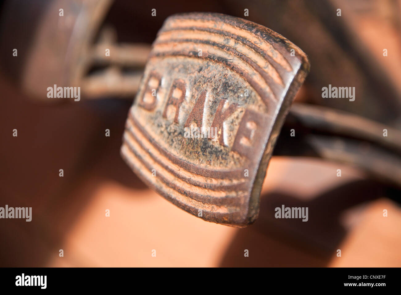 A worn, rusty pedal with BRAKE written on it in a land vehicle, close-up - Stock Image