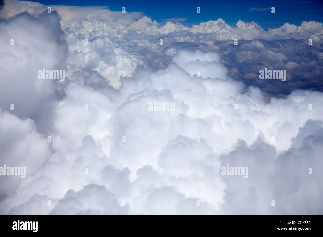 Sunlight on a cloudscape, blue sky in distance - Stock Image