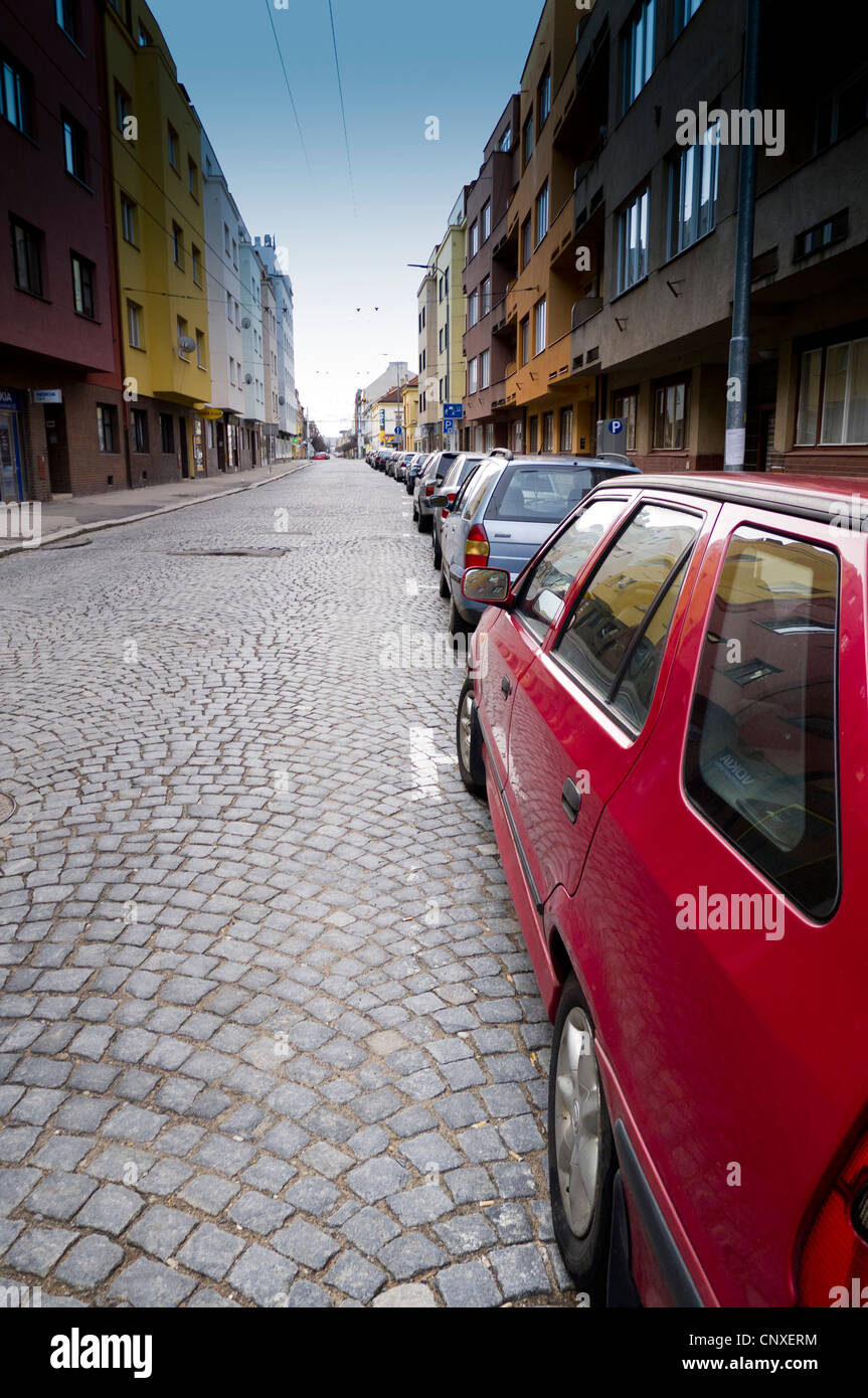 row of cars parked along a city street - Stock Image