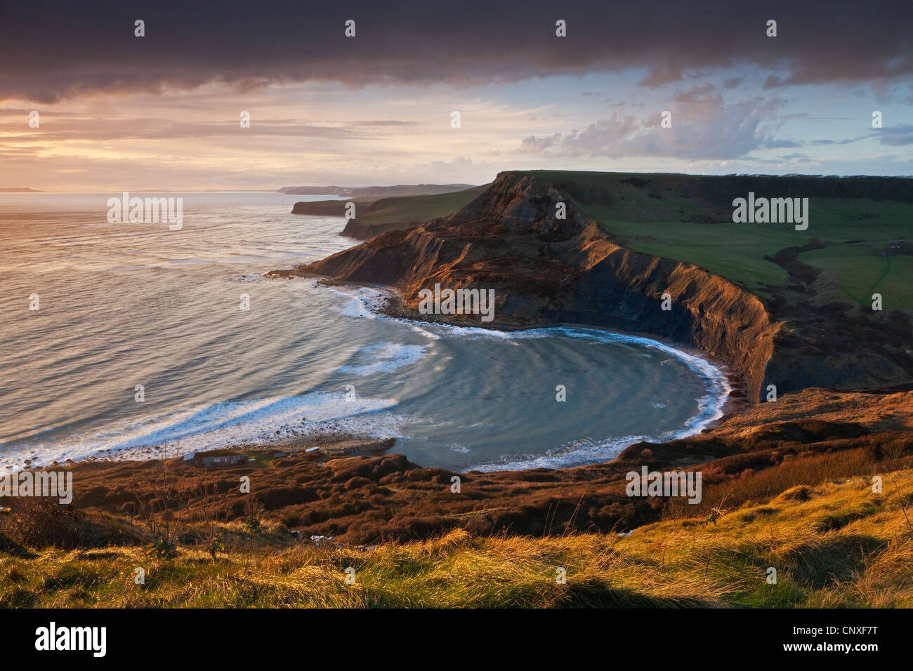 Storm light illuminates Chapmans Pool and Houns Tout cliff, viewed from St Aldhelm's Head, Dorset - Stock Image