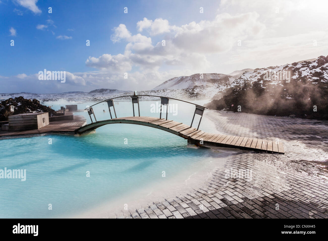 Bridge at the iconic popular Blue Lagoon thermal baths and spa, Iceland, with blue sky, white clouds and steam from - Stock Image