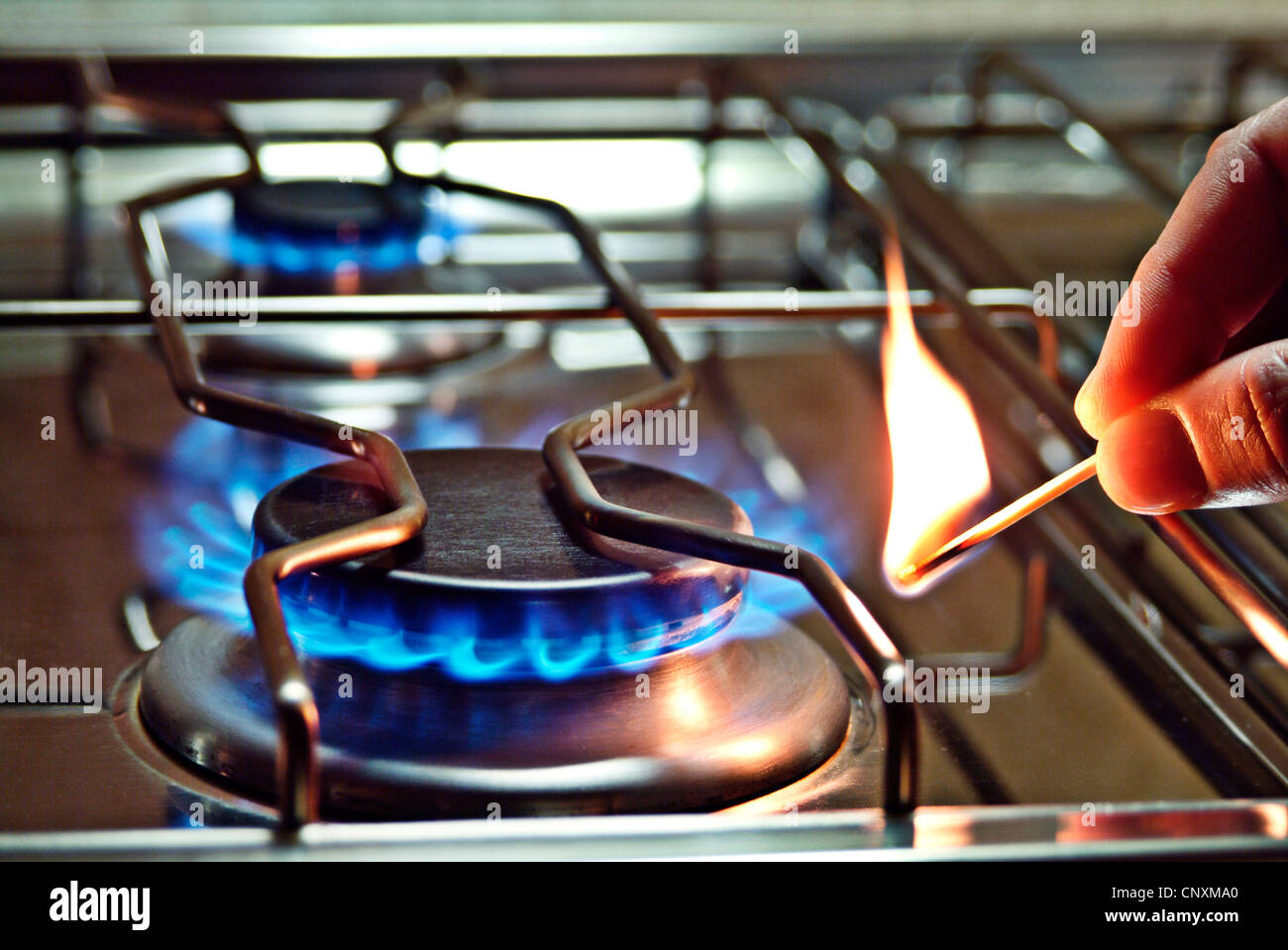Close up of a burner of a gas stove that is lit with a match. - Stock Image
