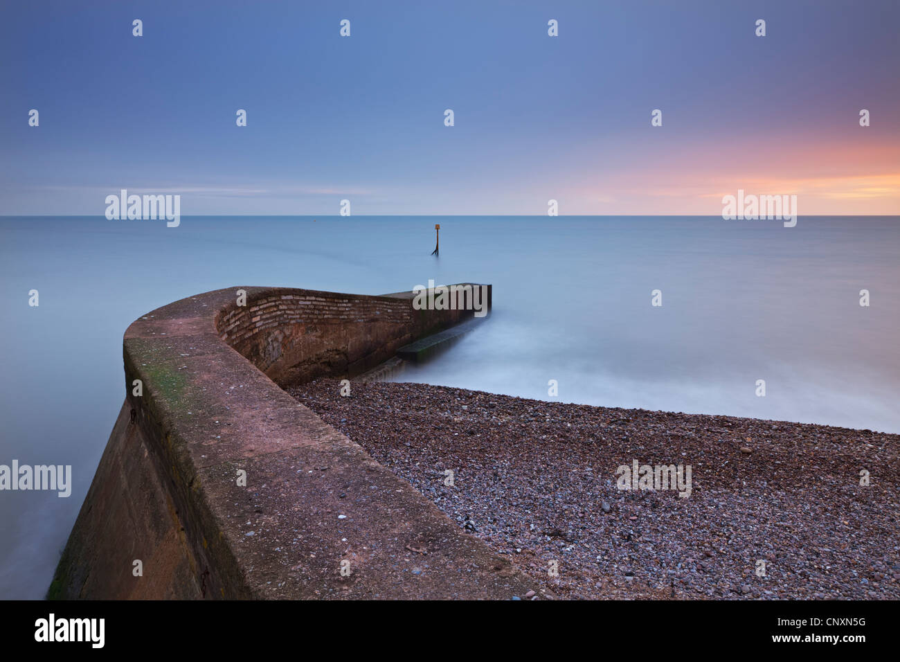 Stone jetty on Sidmouth beachfront at sunset, Sidmouth, Devon, England. Winter (January) 2012. - Stock Image