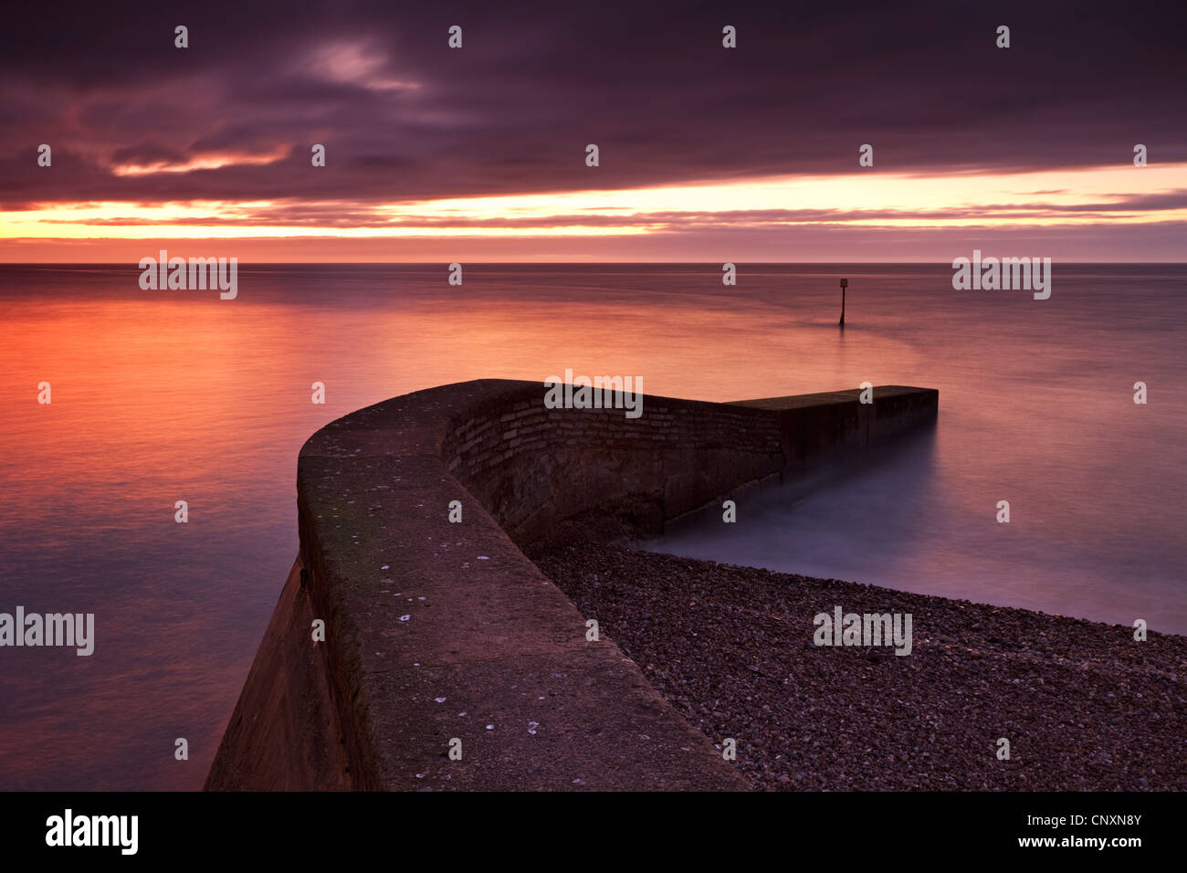 Stone jetty on Sidmouth beachfront at sunrise, Sidmouth, Devon, England. Winter (January) 2012. - Stock Image