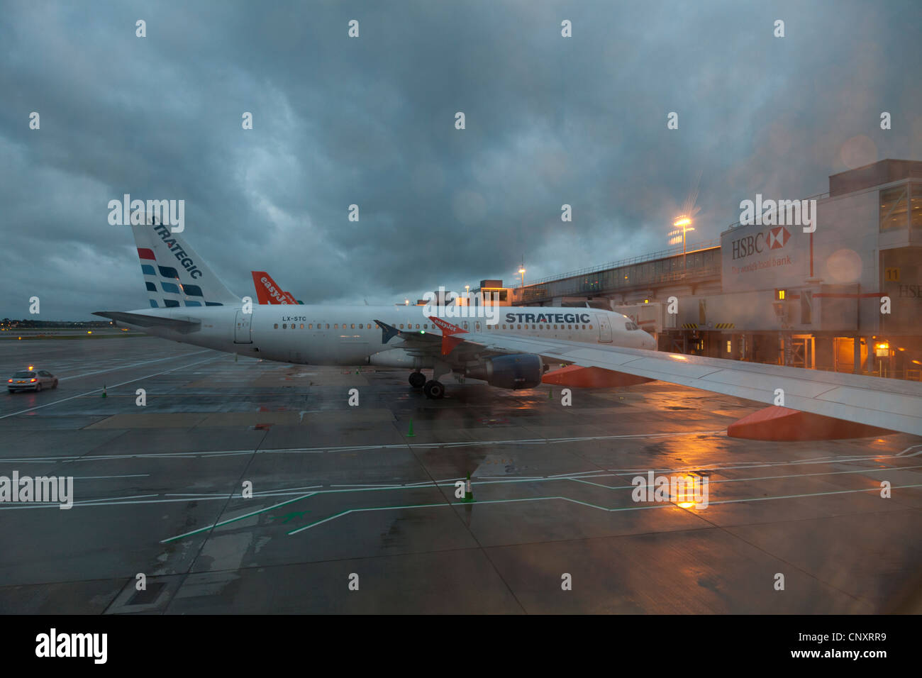 Strategic Airlines aircraft on stand at Gatwick Airport South Terminal in he early morning on a wet and stormy day - Stock Image