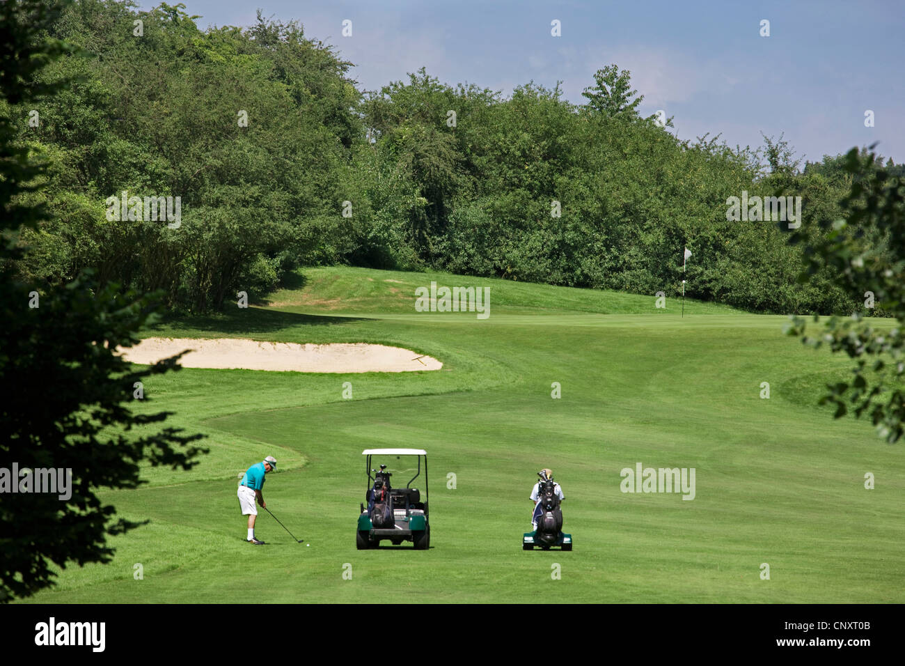 Pensioner with golf cart playing golf on fairway of golf course in Europe - Stock Image