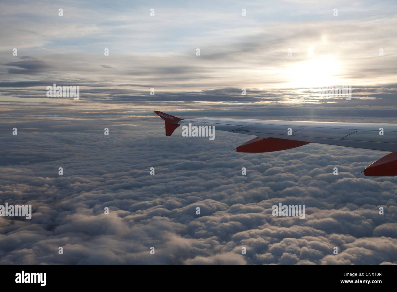 Easyjet aircraft wing above blanket of cloud with rising sun. - Stock Image