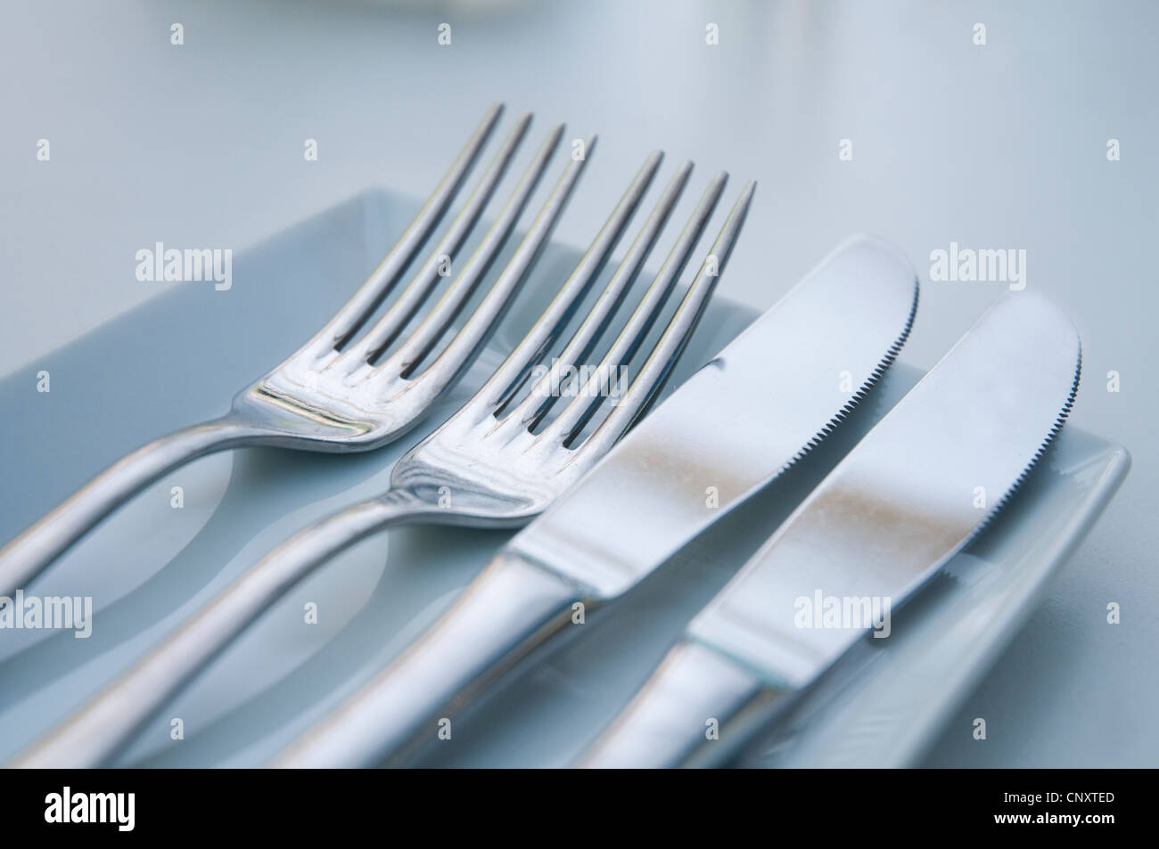 Two forks and two knifes. Close view. - Stock Image