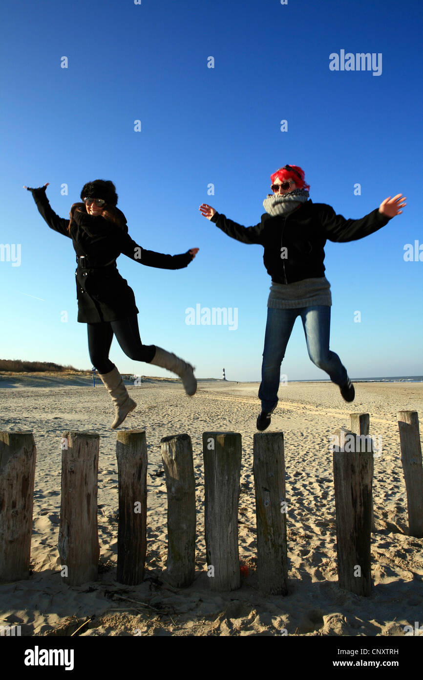 two young women frolicly jumping from groynes at the beach, Netherlands, Zeeland, Breskens, Sluis - Stock Image
