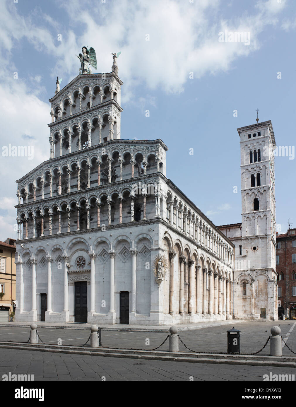 Church of San Michele, Lucca, Italy. Pisan Romanesque 12 th century with tall campanile or bell tower Facade of - Stock Image