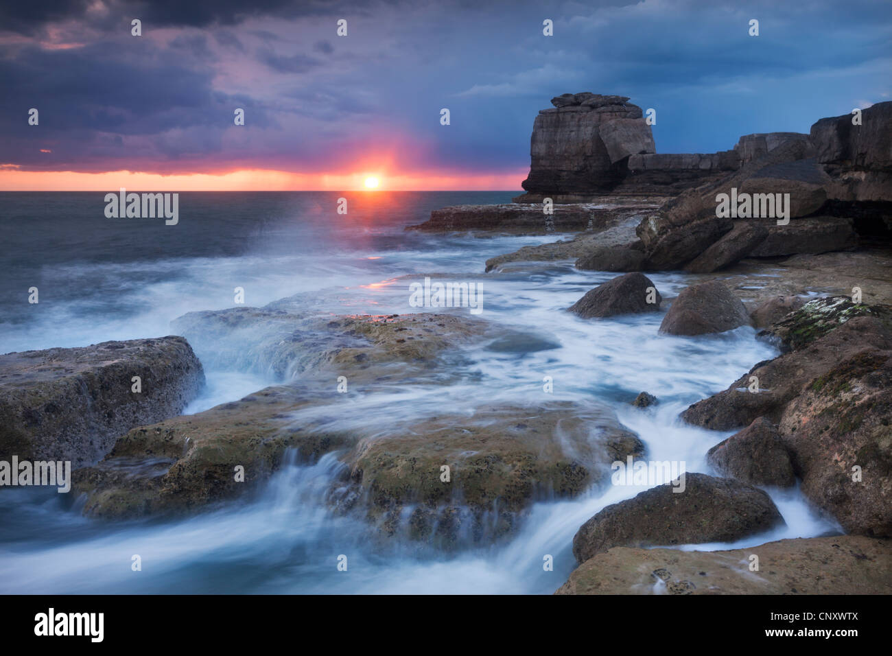 Waves break over the rocky shoreline of Portland Bill, Isle of Portland, Dorset, England. Spring (April) 2012. - Stock Image