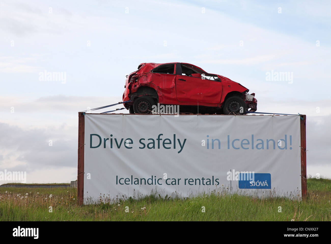 monument at a roadside with a junk car and the warning to drive carefully, Iceland, Gardur - Stock Image