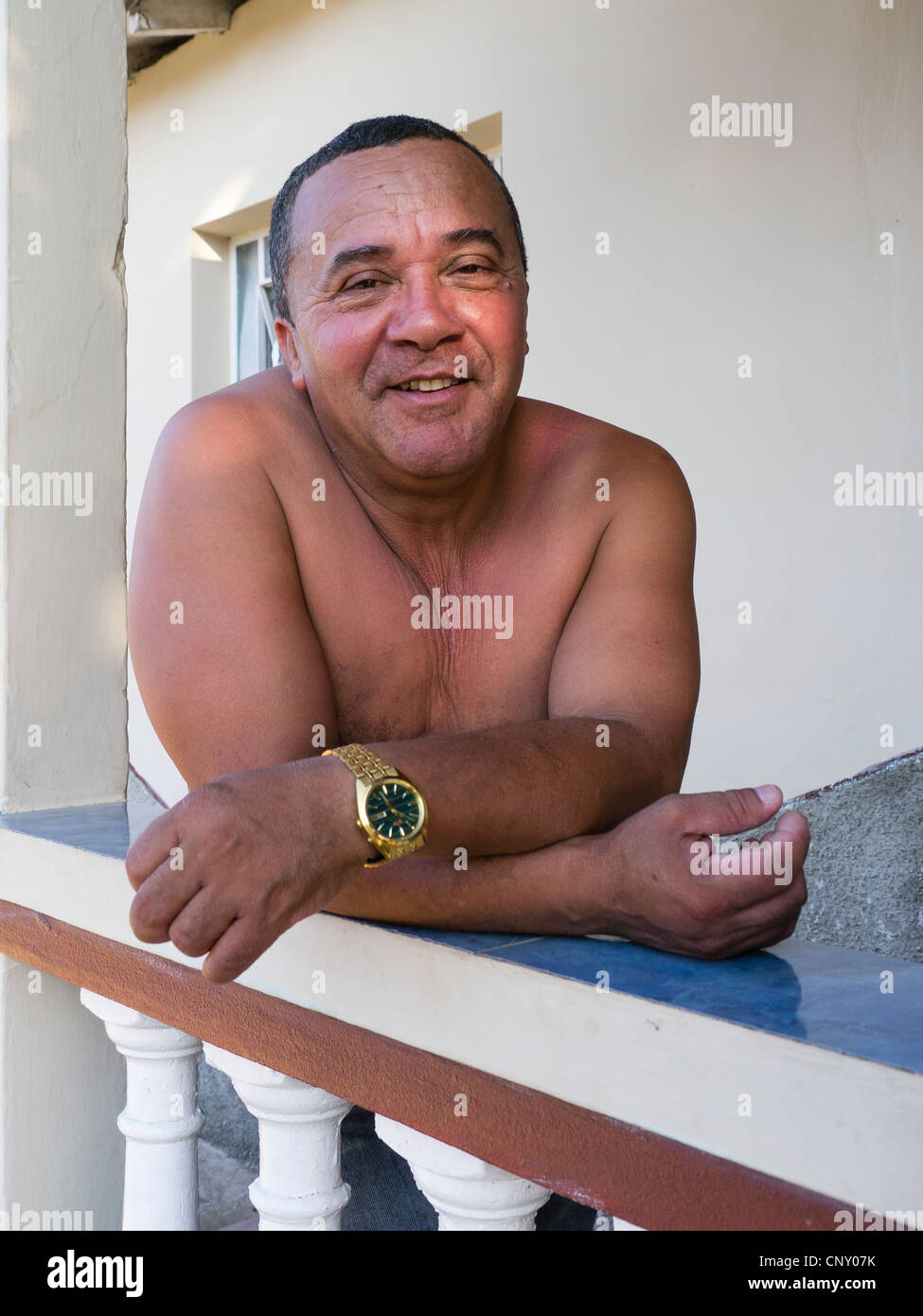 A shirtless 40-45 year old Hispanic Cuban male leans on a balustrade of his house and smiles while looking forward. - Stock Image