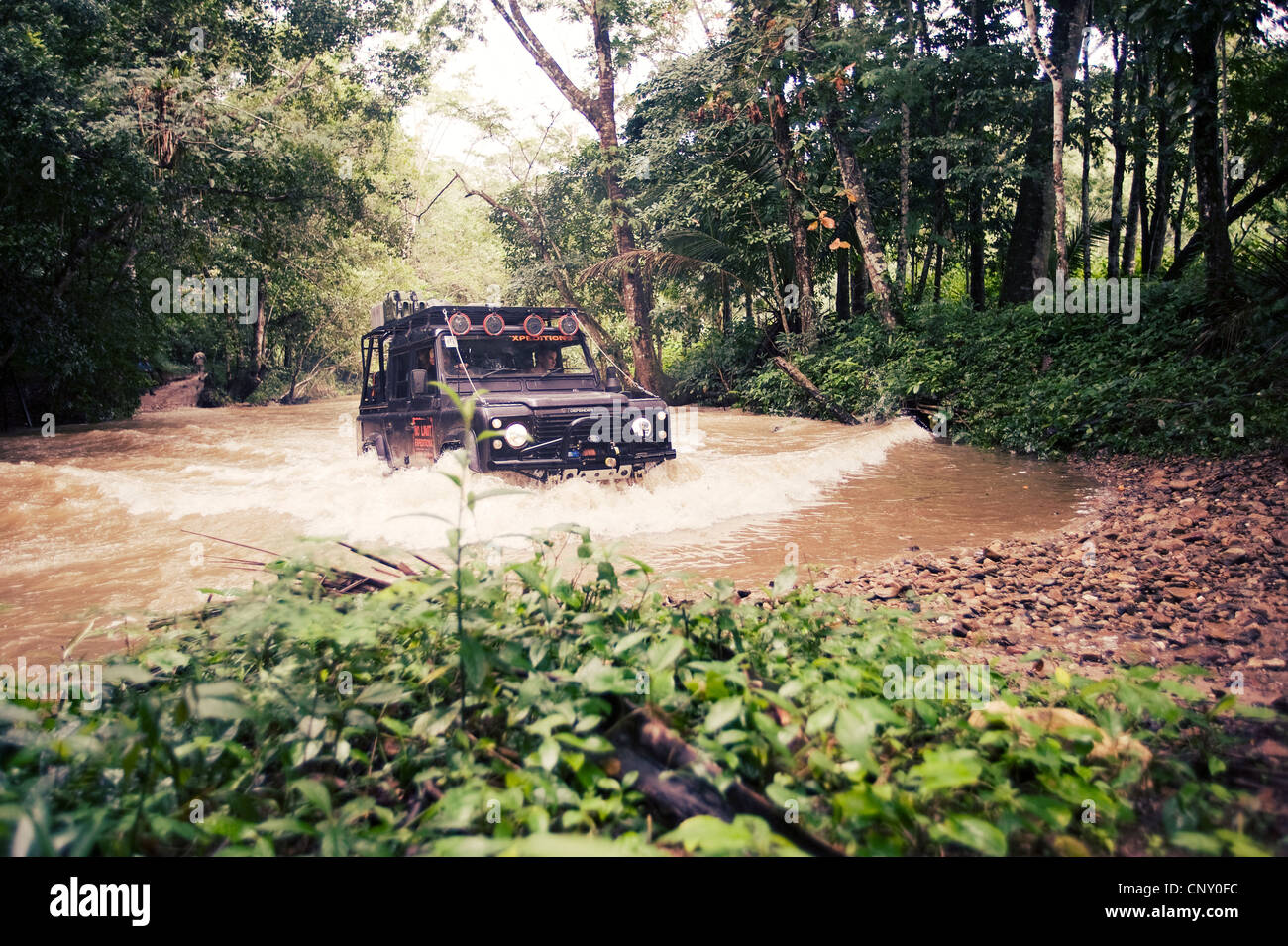 A Land Rover fords a river in Belize - Stock Image