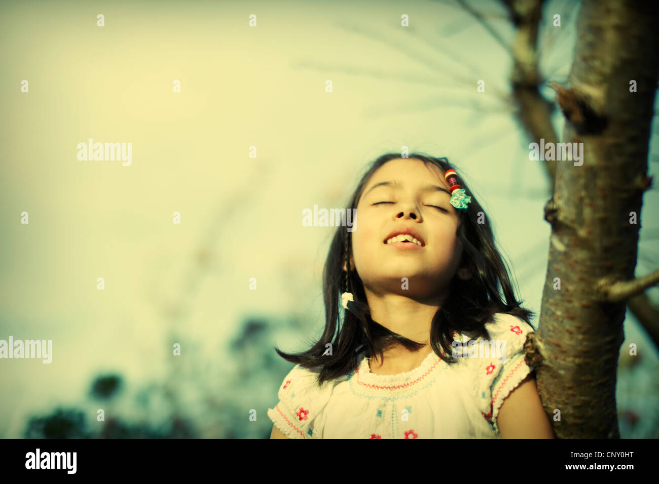 Girl basks in evening sun - Stock Image