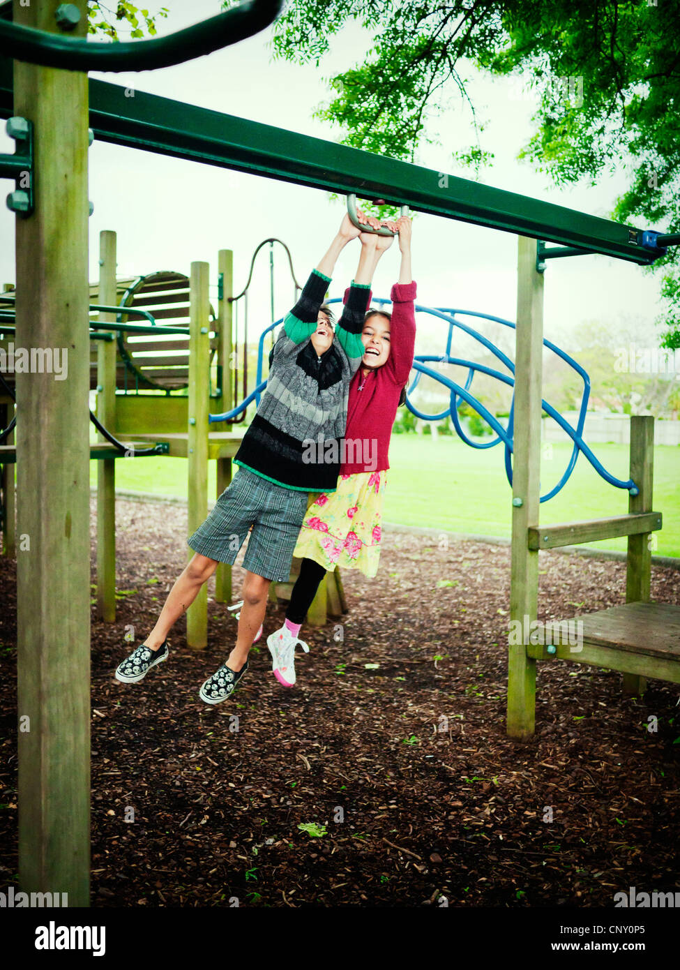 Boy and girl swing together on climbing frame. - Stock Image