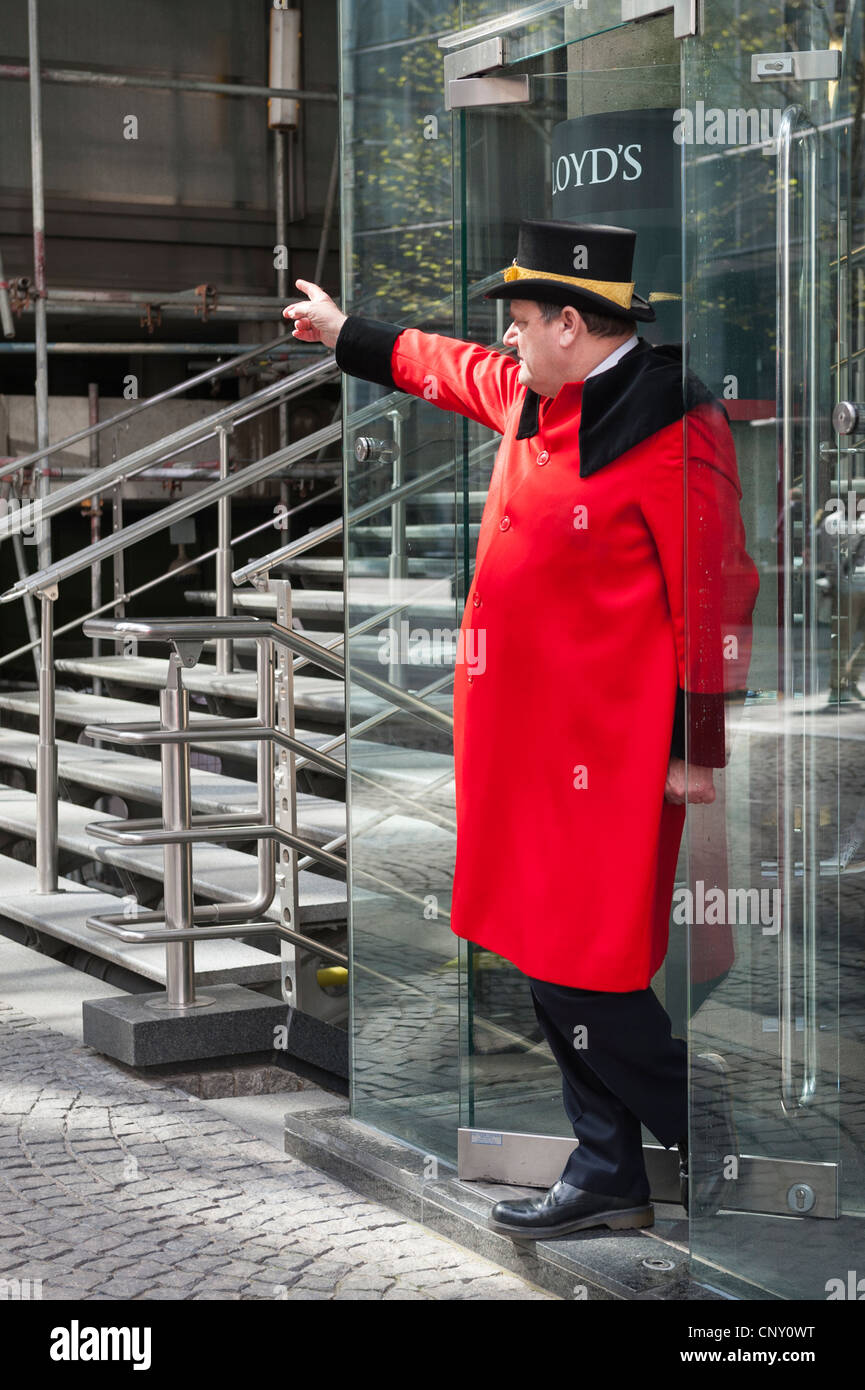 City of London Lloyds doorman concierge porter in traditional red livery frock coat & black top hat trimmed - Stock Image