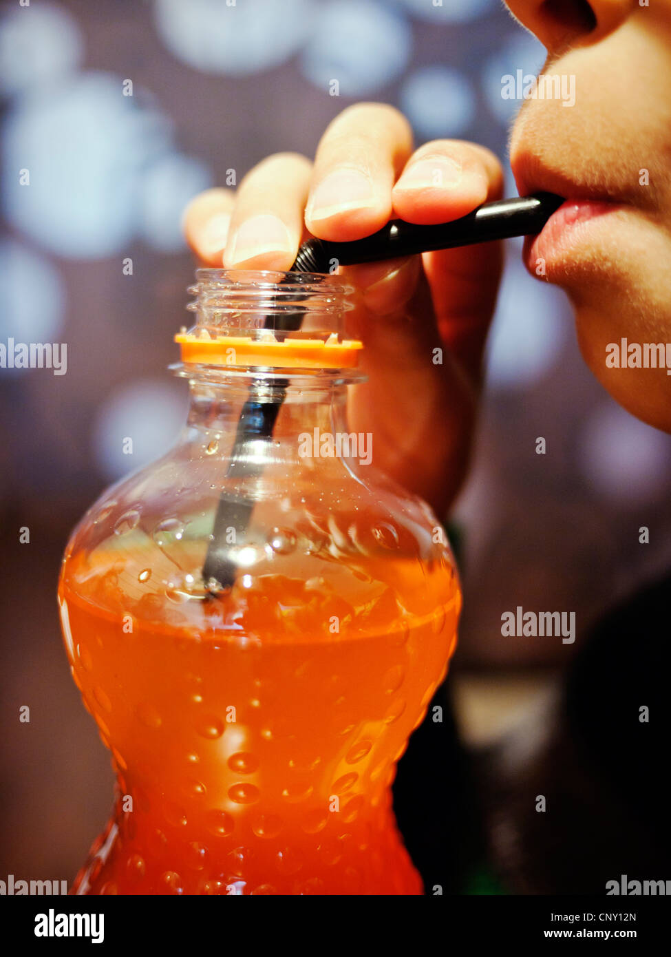 Boy, straw, orange soda. - Stock Image
