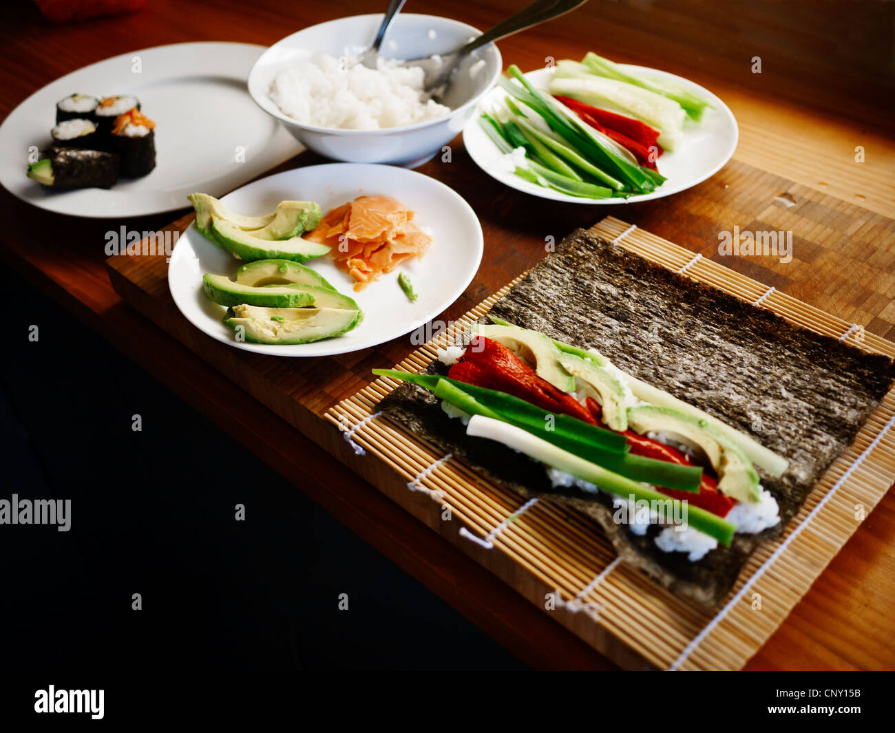 Making sushi at home: smoked salmon, red pepper, avocado, cucmber and spring onion. - Stock Image