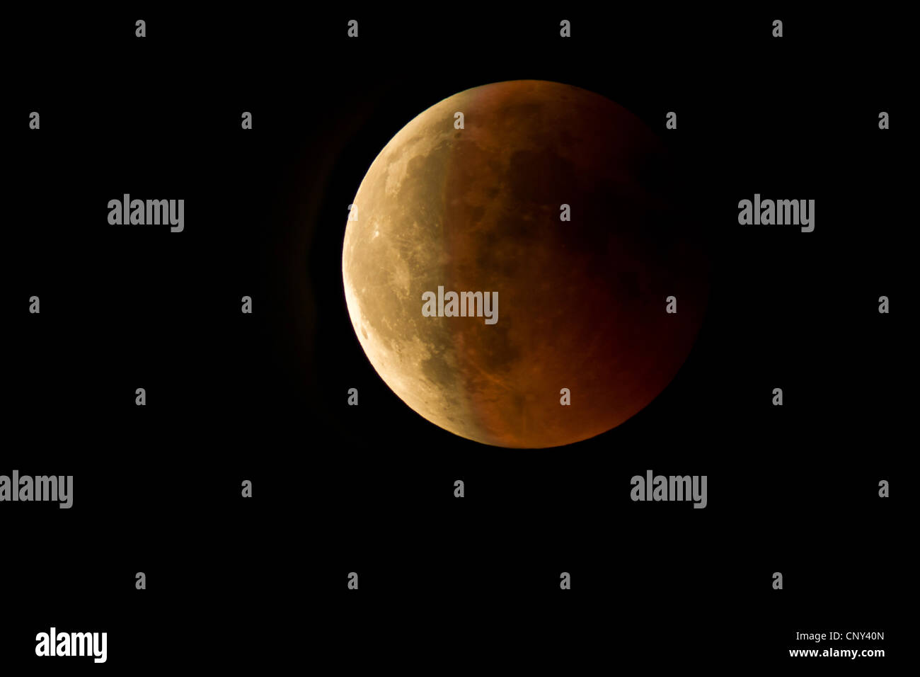 moon eclipse with the lunar globe shimmering redishly in a cloudless sky, Germany, Bavaria - Stock Image