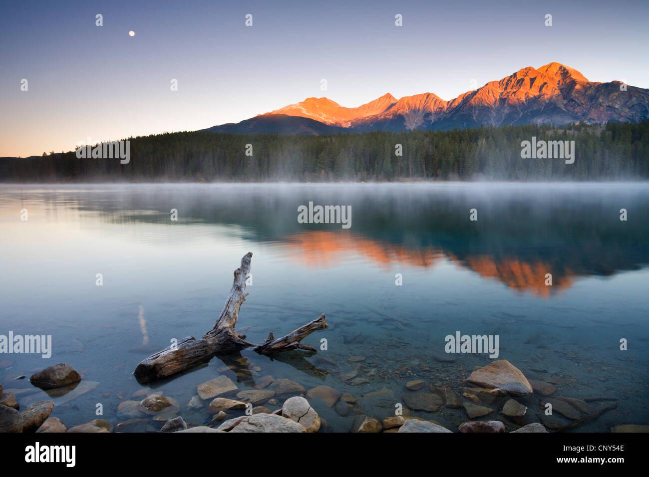 The first rays of sunshine illuminate Pyramid Mountain and reflect in Patricia Lake, Jasper National Park, Alberta, - Stock Image